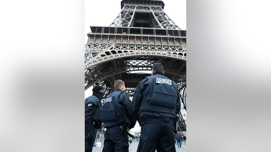 Police forces on patrol pass under the closed Eiffel Tower in Paris, France, Saturday, Nov. 14, 2015, one day after a killing spree orchestrated by ISIS that left 130 people dead. (AP Photo/Kamil Zihnioglu)