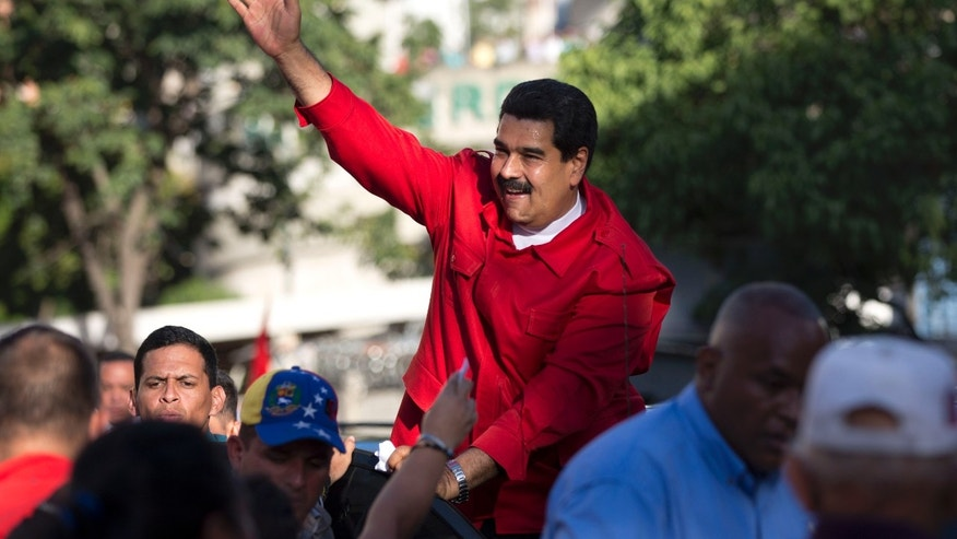 President Maduro waves to supporters in Caracas, Venezuela, Tuesday, Dec. 1, 2015.