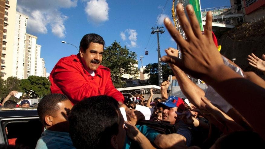 President Maduro greets supporters in Caracas, Venezuela, Tuesday, Dec. 1, 2015.