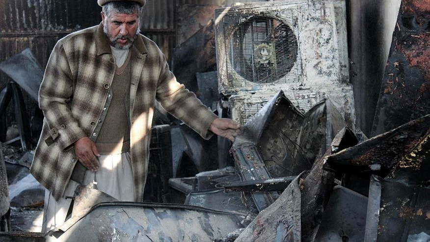 In this Tuesday, Dec. 1, 2015, photo, an Afghan business man salvages what he can from his warehouse that was destroyed from fighting in Kunduz city, north of Kabul, Afghanistan. Two months after the Taliban rampaged through the northern Afghan city of Kunduz, residents are still sifting through the rubble, wondering how they will ever rebuild and worrying that the insurgents will return. (AP Photo/Najim Rahim)