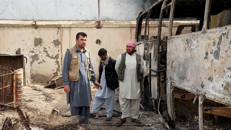 In this Tuesday, Oct. 13, 2015, photo, Afghan businessman Abdul Maroof, left, stands in his warehouse damaged from fighting, in Kunduz, Afghanistan. Two months after the Taliban rampaged through the northern Afghan city of Kunduz, residents are still sifting through the rubble, wondering how they will ever rebuild and worrying that the insurgents will return. (AP Photo)
