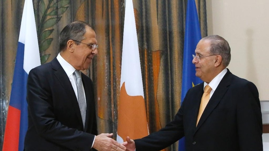 Russian Foreign Minister Sergey Lavrov, left, and Cypriot Foreign Minister Ioannis Kasoulides, shake hands before their talks at the foreign ministry house in Nicosia, on Wednesday, Dec. 2,  2015. Foreign Minister Lavrov is Cyprus for 24 hours official visit. (AP Photo/Petros Karadjias)