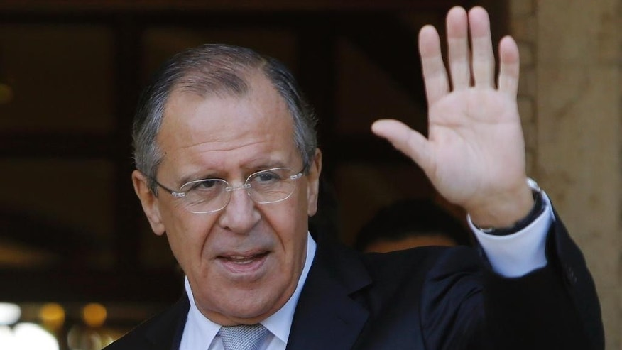 Russian Foreign Minister Sergey Lavrov as he waves to the media after he arrives at the presidential palace for talks with Cyprus' President Nicos Anastasiades in Nicosia, Wednesday, Dec. 2, 2015. (AP Photo/Petros Karadjias)