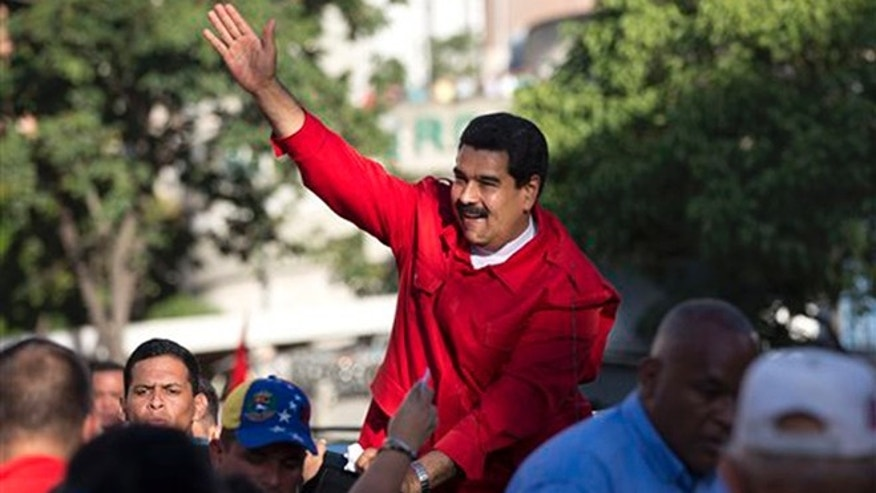 Venezuela's President Nicolas Maduro waves to supporters after the inauguration of cable car public transportation system, in the popular neighborhood of Petare, in Caracas, Venezuela, Tuesday, Dec. 1, 2015. (AP Photo/Ariana Cubillos)