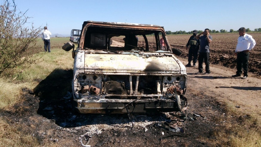In this Nov. 21, 2015 photo, Mexican authorities inspect a burnt out van suspected to belong to a couple of Australian tourists missing for more than a week, in Sinaloa, Mexico. Two burned bodies where reportedly found inside the vehicle. The toursits, Dean Lucas and Adam Coleman were traveling from Edmonton, Canada and were scheduled to arrive on Nov. 21 in the city of Guadalajara but failed to appear. (AP Photo)