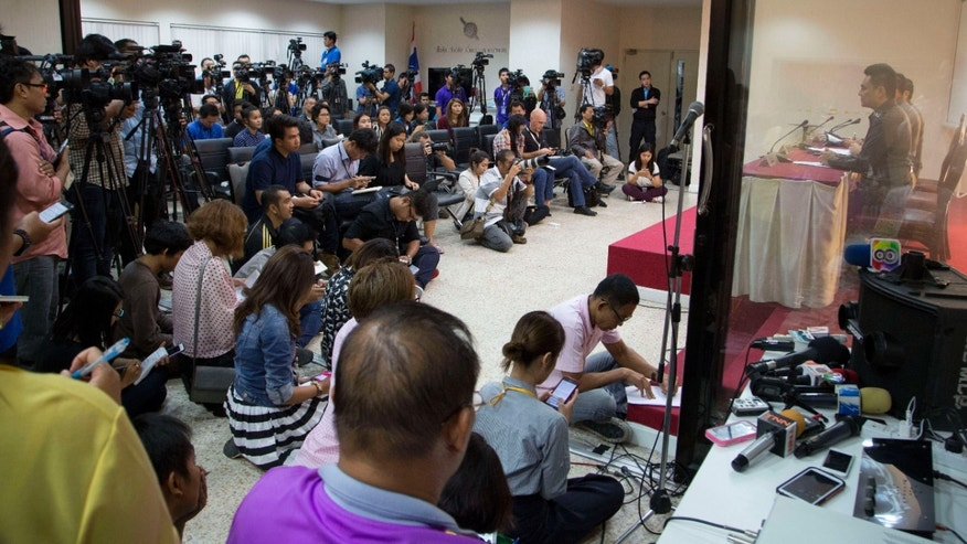 Dec. 4, 2015: Media listen as National police deputy spokesman Col. Songpol Wattanachai addresses a press conference in Bangkok, Thailand.