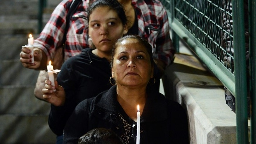Elda Flores, center, stands with her daughter and grandchildren during a candlelight vigil for victims of a shooting, Thursday, Dec. 3, 2015, at San Manuel Stadium in San Bernardino, Calif. A husband and wife opened fire on a holiday banquet, killing multiple people on Wednesday. Hours later, the couple died in a shootout with police. (Jose Huerta/The Victor Valley Daily Press via AP) MANDATORY CREDIT