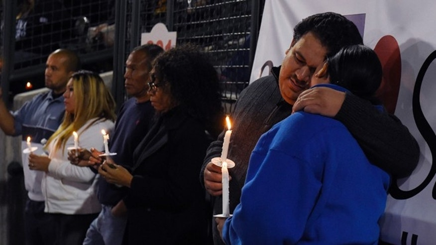 A couple hugs during a candlelight vigil at San Manuel Stadium, Thursday, Dec. 3, 2015, in San Bernardino, Calif. for multiple victims of a shooting that took place at a holiday banquet on Wednesday. A husband and wife opened fire killing multiple people on Wednesday. Hours later, the couple died in a shootout with police. (AP Photo/Mark J. Terrill)