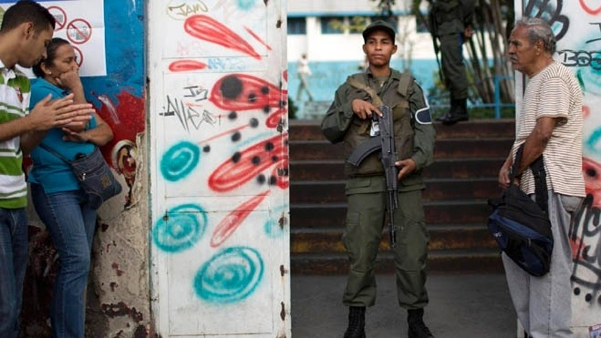 Dec. 6, 2015: A National Guard soldier stand guard at the entrance of a polling station during congressional elections in Caracas, Venezuela.