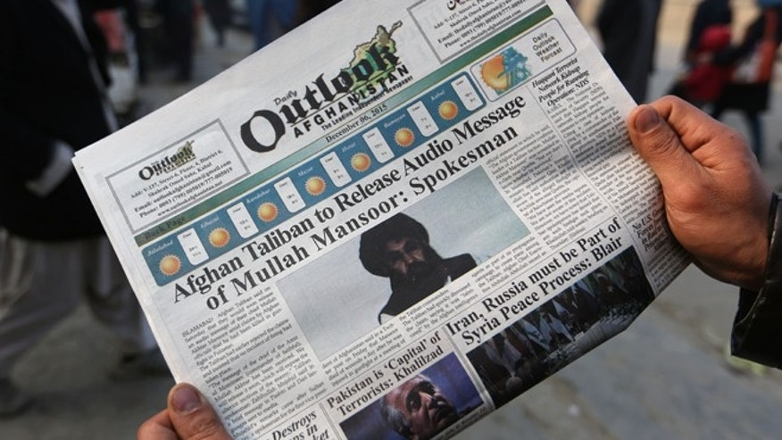 An Afghan man reads a local newspaper with photos of the new leader of the Afghan Taliban, Mullah Akhtar Mansoor.