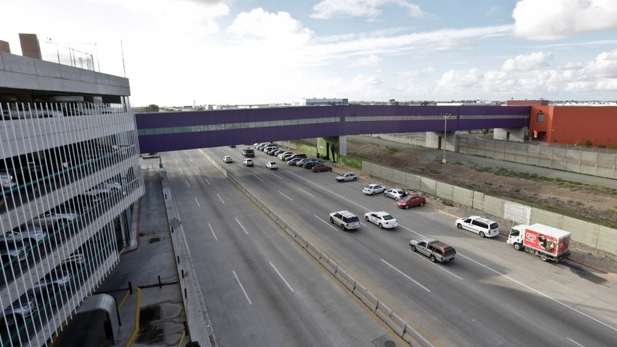 In this Wednesday, Nov. 25, 2015 photo taken in Tijuana, Mexico, vehicles pass under a walking bridge that connects the new Cross Border Xpress air terminal in San Diego, right, to the Tijuana International Airport, left. The new terminal is scheduled to begin operations on Wednesday, Dec. 9. (AP Photo/Lenny Ignelzi)
