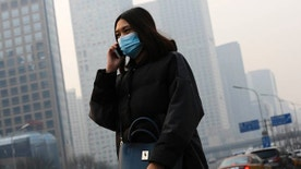 Dec. 7, 2015: A woman wearing a mask to protect herself from pollutants walks past office buildings shrouded with pollution haze in Beijing. Smog shrouded the capital city Monday after authorities in Beijing issued an orange alert on Saturday.