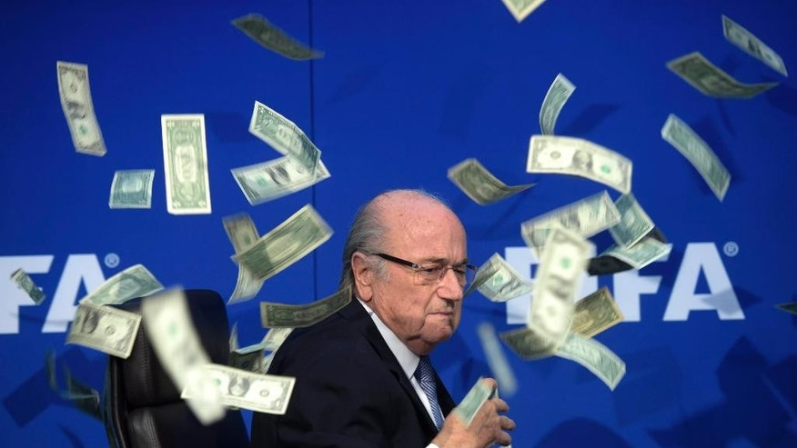 FOR USE AS DESIRED, YEAR END PHOTOS - FILE - FIFA president Sepp Blatter is surrounded by banknotes thrown by British comedian Simon Brodkin during a press conference following the Extraordinary FIFA Executive Committee meeting at the headquarters in Zurich, Switzerland, Monday, July 20, 2015.  Blatter and FIFA have been engulfed in a deepening corruption scandal as the sport faces criminal investigations in Switzerland and the US.  (Ennio Leanza/Keystone via AP, File) MANDATORY CREDIT