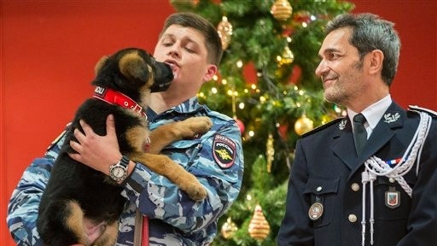 A Russian police officer presenting the puppy to French police.