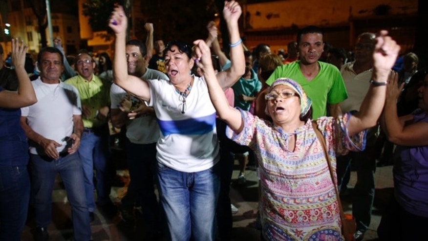 Dec. 6, 2015: Opposition supporters celebrates the closing of a polling station during congressional elections in Caracas, Venezuela. Some members of the opposition are angry after elections officials ordered polling centers to stay open for an extra hour, even if no one was standing in line to vote. Government opponents mobbed some voting stations demanding that the National Guard stick to the original schedule of closing at 6 p.m. (AP Photo/Ariana Cubillos)