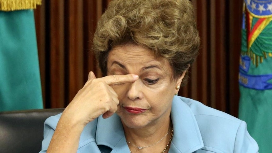 Brazil's President Dilma Rousseff touches her face during a meeting with state governors regarding the impeachment process opened against her at Planalto presidential palace, in Brasilia, Brazil, Tuesday, Dec. 8, 2015. On Tuesday, parties are expected to nominate representatives for a special commission in the lower house to determine whether impeachment proceedings will go to a full vote in the house. The proceedings were introduced last week, citing a court's finding that Rousseff's administration violated fiscal responsibility laws by using money from state-run banks to fill budget gaps and pay for social programs. (AP Photo/Eraldo Peres)