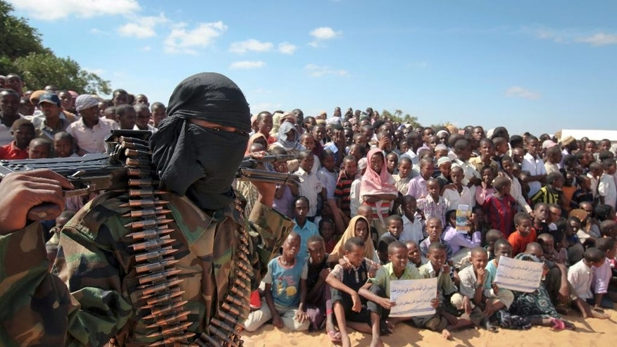 FILE - In this Monday, Feb. 13, 2012 file photo, an armed member of the militant group al-Shabab attends a rally in support of the merger of the Somali militant group al-Shabab with al-Qaida, on the outskirts of Mogadishu, Somalia. The defections of two American Islamic extremist fighters in Somalia highlight tensions within the insurgent group al-Shabab over whether it should remain affiliated to al-Qaida or switch allegiance to the Islamic State group, according to an al-Shabab commander Tuesday, Dec. 8, 2015. (AP Photo, File)