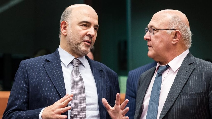 France's Finance Minister Michel Sapin, right, talks with European Commissioner for Economic and Financial Affairs Pierre Moscovici during an Eurogroup finance ministers meeting at the EU Council building in Brussels on Monday, Dec. 7, 2015. (AP Photo/Geert Vanden Wijngaert)