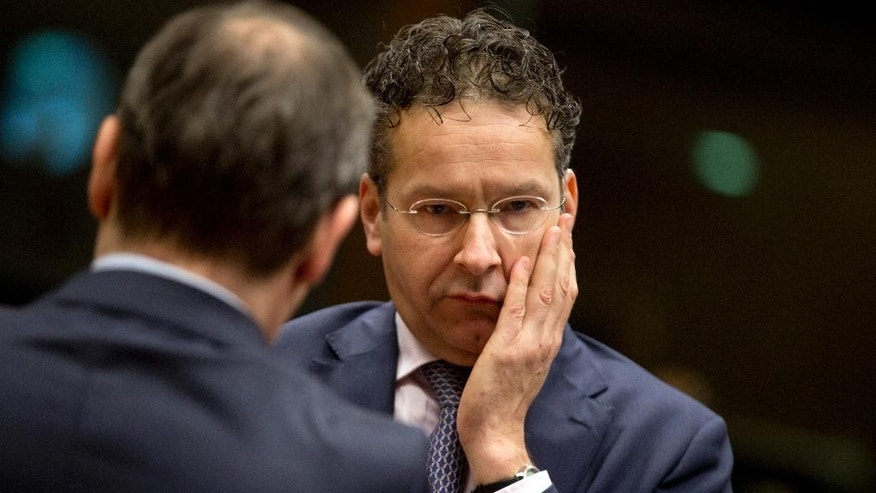 Dutch Finance Minister Jeroen Dijsselbloem, right, speaks with a member of his delegation during a meeting of EU finance ministers at the EU Council building in Brussels on Tuesday, Dec. 8, 2015. EU finance ministers are set to debate in Brussels ways to better track financial transfers, control pre-pay bank cards, freeze assets and limit movements of cash and precious metals. (AP Photo/Virginia Mayo)