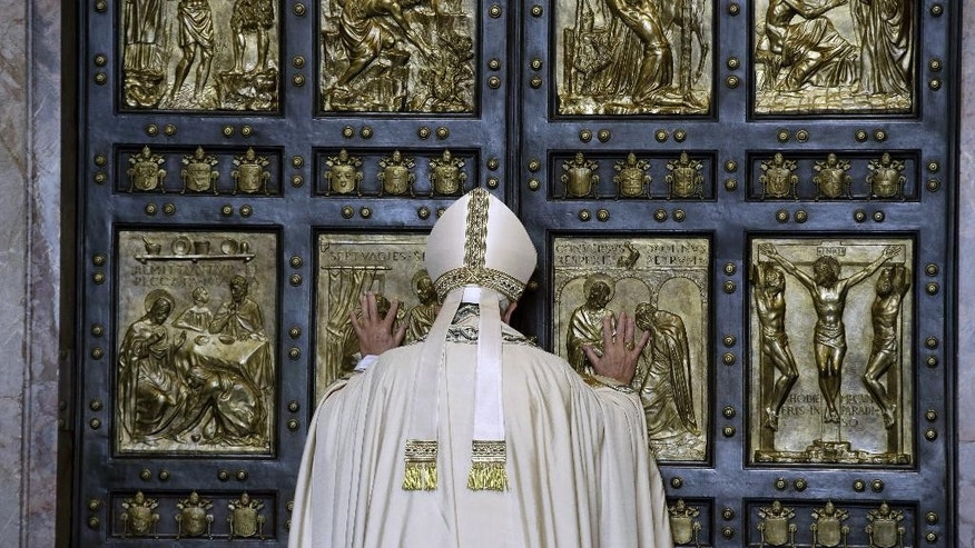 Pope Francis pushes open the Holy Door of St. Peter's Basilica, formally launching the Holy Year of Mercy, at the Vatican, Tuesday, Dec. 8, 2015. The 12-month jubilee emphasizes what has become the leitmotif of his papacy: to show the merciful and welcoming side of a Catholic Church more often known for its moralizing and judgment. (AP Photo/Gregorio Borgia)