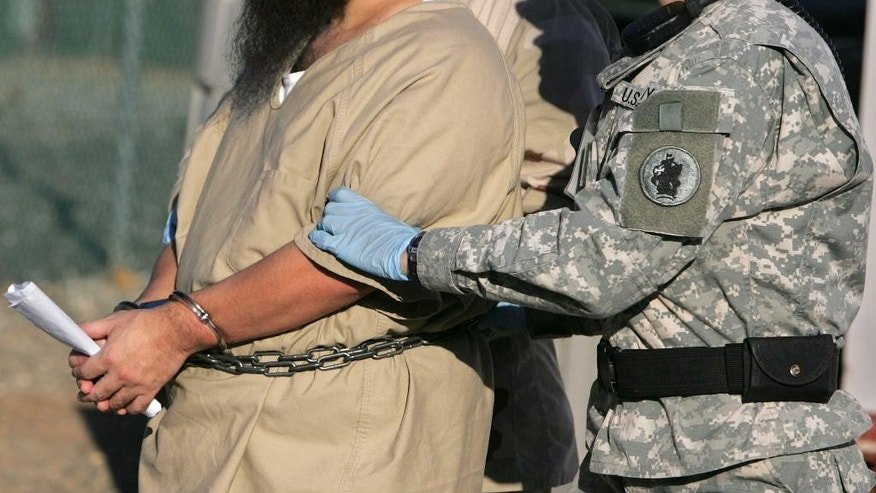 FILE - In this Dec. 6, 2006 file photo, reviewed by a U.S. Dept of Defense official, a shackled detainee is transported by a female guard, front, and male guard, behind, away from his annual Administrative Review Board hearing with U.S. officials, at Camp Delta detention center, Guantanamo Bay U.S. Naval Base, Cuba. A military judge has refused on Thursday, Dec. 10, 2015, to lift an order barring female guards at Guantanamo from having physical contact with five men charged in the Sept. 11 terrorist attack. Army Col. James Pohl denied a request by prosecutors to lift a temporary order he imposed in January. (AP Photo/Brennan Linsley, File)