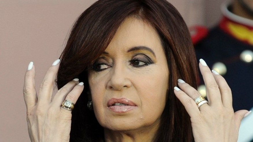 FILE - In this Dec. 10, 2011 file photo, Argentina's President Cristina Fernandez pushes her hair back at government house, during her inaugural festivities in Buenos Aires, Argentina. A growing spat between Argentina's outgoing president and president elect over inauguration day logistics took a strange turn on Friday, Dec. 4, 2015. President-elect Mauricio Macri wants to receive the presidential baton and sash from outgoing Fernandez in the government house, or Casa Rosada, during the Dec. 10 inauguration. However, Fernandez administration officials insist the transfer will happen in Congress.  (AP Photo/Jorge Araujo, File)