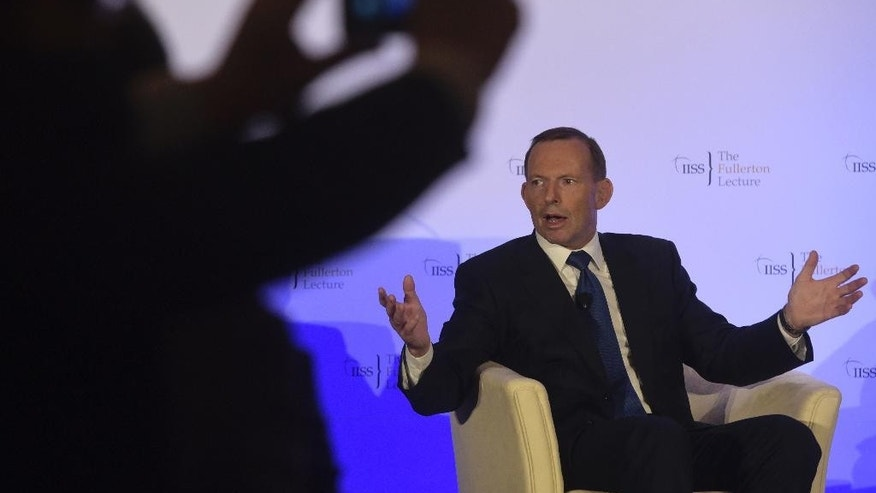 A member of the audience, left, takes a picture of former Australian Prime Minister Tony Abbott, right, as he responds during a question and answer session after delivering a lecture at the Fullerton Hotel in Singapore on Wednesday, Dec. 9, 2015 (AP Photo/Joseph Nair)
