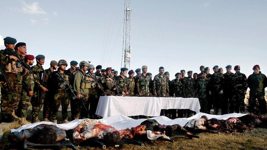 Afghan security forces stand in front of dead bodies of Taliban fighters after clashes in Kandahar Airfield, Afghanistan, Wednesday, Dec. 9, 2015. A Taliban assault on an airport in the southern Afghan city of Kandahar that has been underway for nearly 24 hours has killed dozens of people, the Defense Ministry said Wednesday. (AP Photos/Allauddin Khan)