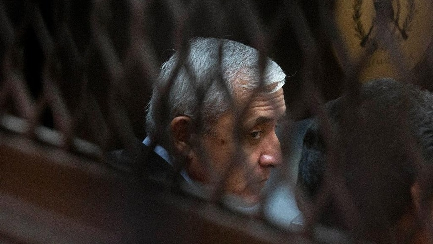 FILE - In this Sept. 8, 2015, file photo, Guatemala's former president Otto Perez Molina, photographed through a window, sits in court for a third hearing on corruption allegations that led him to resign, in Guatemala City. The court is considering allegations that Perez Molina was involved in a scheme in which businesspeople paid bribes to avoid import duties through Guatemala's customs agency. (AP Photo/Esteban Felix, File)