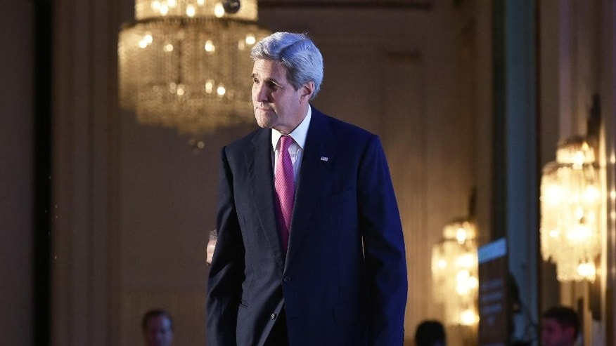 US Secretary of State John Kerry stands on the stage during the International New York Times Energy for Tomorrow Conference at the Hotel Potocki in Paris, France, Dec. 9, 2015 on the sidelines of the COP21 United Nations conference on climate change. (AP Photo/Mandel Ngan, Pool via the AP)