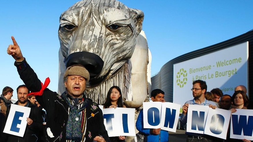 Chief Bill Erasmus of the Dene nation, Northern Canada, center, gestures with activists from Greenpeace during a protest in front of a two-story-high, mechanically operated polar bear called Aurora into the conference venue, to represent everyone hoping in the next 72 hours during the COP21, United Nations Climate Change Conference in Le Bourget, north of Paris, France,  Wednesday, Dec. 9, 2015. (AP Photo/Francois Mori)