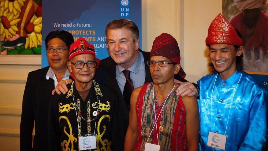 U.S. actor and activist Alec Baldwin poses with representants of the Komunitas Adat Muara Tae from Indonesia NGo prior to The Equator Prize Award ceremony at Theatre Mogador, in Paris, Monday, Dec. 7, 2015 as part of the COP21, United Nations Climate Change Conference. The Equator Prize 2015 honors local achievement and mobilize action for people, nature and climate. (AP Photo/Francois Mori)