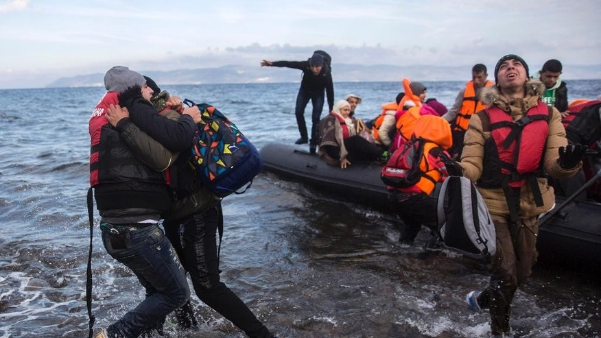 Migrants and refugees react as they arrive on a dinghy from the Turkish coast to the northeastern Greek island of Lesbos on Wednesday, Dec. 9, 2015. Greek authorities said in an incident at the southeastern Greek islet of Farmakonissi a number of people have died and others are missing after a boat carrying migrants sank in Aegean Sea. (AP Photo/Santi Palacios)