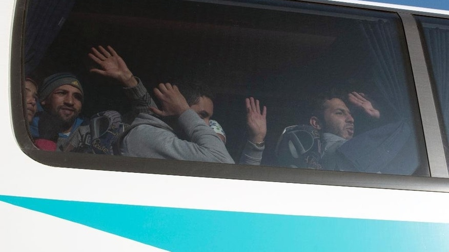 Stranded migrants wave to the media behind a bus window as they leave from the Greek-Macedonian border to Athens after a police operation near the northern Greek village of Idomeni, Wednesday, Dec. 9, 2015. More than 200 riot police have been deployed to the border area at Idomeni following the standoff that has halted freight rail services from Greece to other European countries. (AP Photo/Giannis Papanikos)