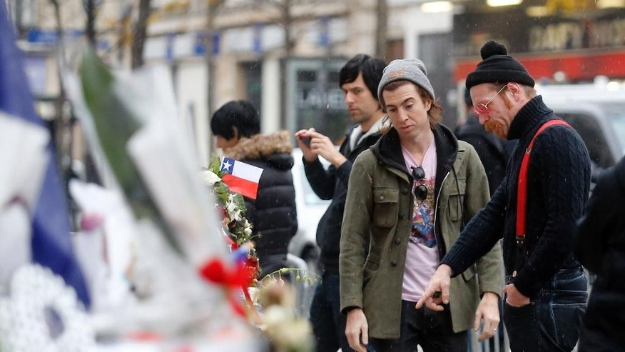 Members of the band Eagles of Death Metal, Jesse Hughes, right, and Julian Dorio pay their respects to 89 victims who died in a Nov. 13 attack at the Bataclan concert hall in Paris, France, Tuesday, Dec. 8, 2015. Members of the California rock band Eagles of Death Metal are back at the ravaged Paris theater where they survived a massacre by Islamic extremist suicide bombers. (AP Photo/Jacques Brinon)