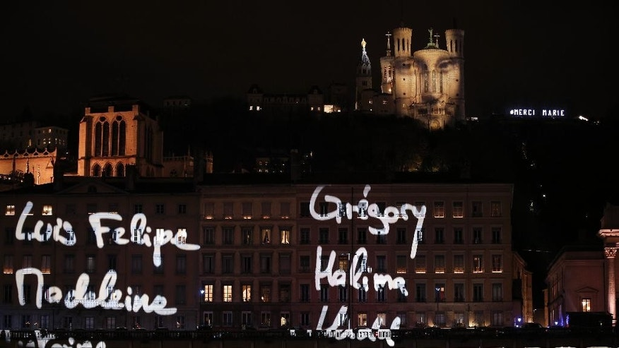 The first names of the 130 Paris attacks victims are spread over buildings in Lyon, central France, during a projection of French artist Daniel Knipper, Tuesday, Dec. 8, 2015.  Each year, millions of visitors come into the city to watch the Festival des Lumieres, and this year the Lyon municipality has decided to cancel the festival to express solidarity with the victims. (AP Photo/Laurent Cipriani)