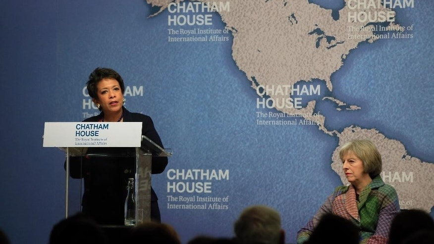 United States Attorney General Loretta Lynch, left, speaks at Chatham House, The Royal Institute for International Affairs, as the British Home Secretary Theresa May looks on in London, Wednesday, Dec. 9, 2015. (AP Photo/Alastair Grant)