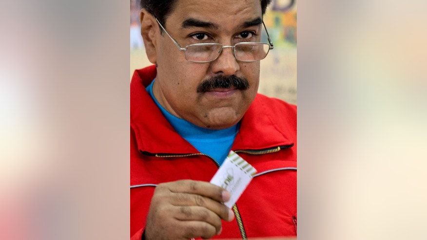 "Venezuela's President Nicolas Maduro holds up his electronic voting receipt before placing it in a box during congressional elections in Caracas, Venezuela, Sunday, Dec. 6, 2015. Maduro had repeatedly vowed in recent weeks to take to the streets if his party lost. But the president changed his tone on Saturday, saying: ""In Venezuela, peace and democracy must reign. I've said we'll take the fight to the streets, but maybe I was wrong."" (AP Photo/Ariana Cubillos)"