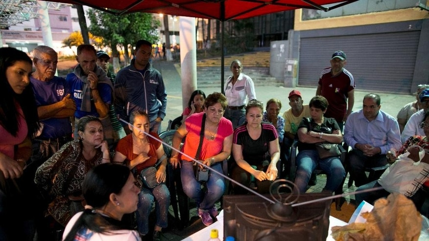 Pro-government supporters watch the latest election information from National Electoral Council, on a television set, outside of a polling station in Caracas, Venezuela, Sunday, Dec. 6, 2015. Some members of the opposition are angry after elections officials ordered polling centers to stay open for an extra hour, even if no one was standing in line to vote, during the day's congressional elections. Government opponents mobbed some voting stations demanding that the National Guard stick to the original schedule of closing at 6 p.m. (AP Photo/Alejandro Cegarra)
