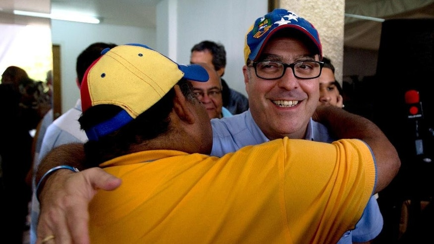 Opposition lawmaker Julio Borges, who was reelected to Congress, is congratulated by a supporter before a news conference in Caracas, Venezuela, Monday, Dec. 7, 2015. Venezuela's opposition won control of the National Assembly by a landslide in Sunday's election, stunning the ruling party and altering the balance of power 17 years after the late Hugo Chavez was elected president. (AP Photo/Fernando Llano)