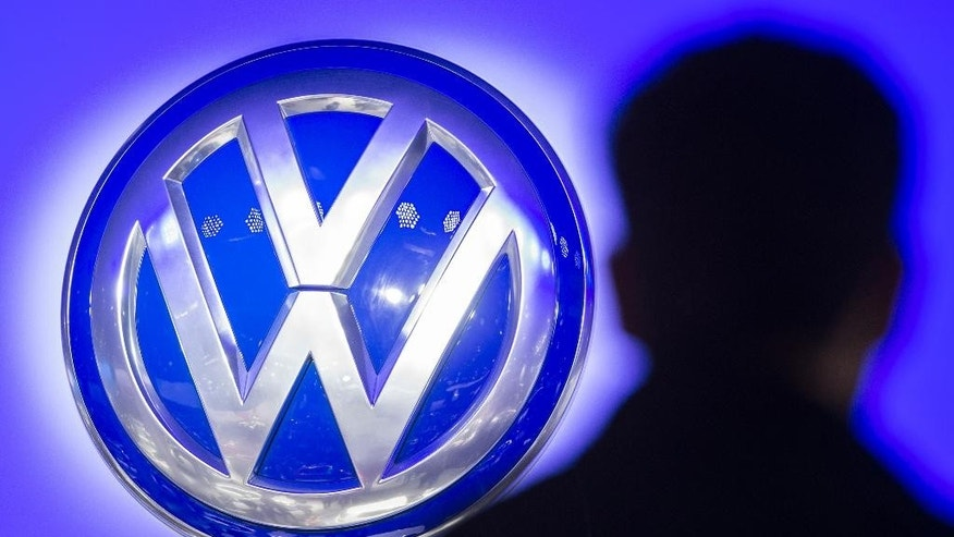 "FILE - In this Sept. 23, 2015 file photo the silhouette of visitor pictured next to the logo of German car manufacturer Volkswagen AG at the International Motor Show IAA in Frankfurt, Germany. Volkswagen said Wednesday, Dec. 9, 2015, that a problem with carbon dioxide emissions is far smaller than initially suspected, with further checks finding ""slight discrepancies"" in only a few models and no evidence of illegal changes to fuel consumption and emissions figures. (Boris Roessler/dpa via AP, File)"