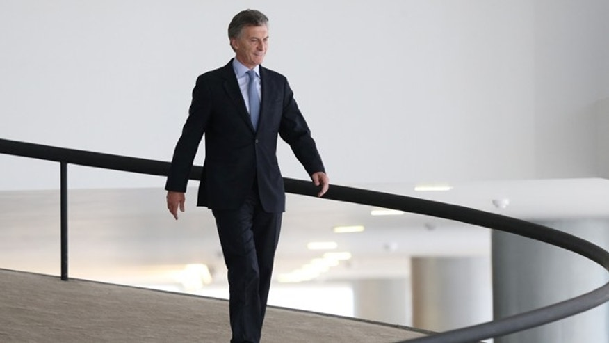 In this Friday, Dec. 4, 2015 photo, Argentina's President-elect Mauricio Macri walks down an inner ramp of the Planalto Presidential Palace, after meeting with Brazils President Dilma Rousseff, in Brasilia, Brazil. Macri, who won a presidential runoff election over the ruling party candidate in late November, is making his first official state visit as the next leader of Argentina. (AP Photo/Eraldo Peres)