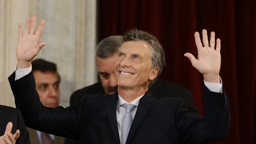Mauricio Macri waves after being sworn in as new president at the Congress in Buenos Aires, Argentina, Thursday, Dec. 10, 2015. Macri was sworn in, inheriting myriad economic problems from the often divisive outgoing President Cristina Fernandez, who skipped the inauguration in a final sign of defiance that underscored deep polarization in the South American nation. (AP Photo/Ricardo Mazalan)
