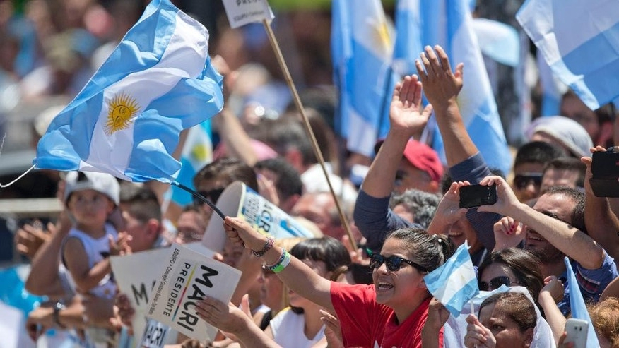 Supporters of Argentina's President Mauricio Macri wave Argentine flags as he arrives to Argentina's Congress to be sworn in, in Buenos Aires, Argentina, Thursday, Dec. 10, 2015. Macri was sworn in, inheriting myriad economic problems from the often divisive outgoing President Cristina Fernandez, who skipped the inauguration in a final sign of defiance that underscored deep polarization in the South American nation. (AP Photo/Natacha Pisarenko)