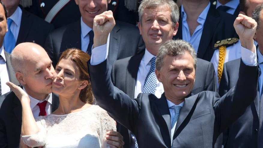Argentina President Mauricio Macri, right, greets followers as he leaves Argentina's Congress after being sworn in, in Buenos Aires, Argentina, Thursday, Dec. 10, 2015. The mayor of the City of Buenos Aires Horacio Rodriguez Larreta, left, kisses first lady Juliana Awada. Macri assumes power promising many changes, replacing President Cristina Fernandez after 8 years in office. (AP Photo/Maria Natacha Pisarenko)