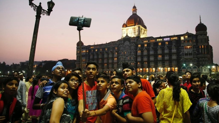 In this Saturday, Dec. 5, 2015 photo, Indian students take a selfie in front of the Taj Mahal hotel in Mumbai, India. India's financial hub of Mumbai has an annual GDP of about $151 billion, along with some 2.8 million people crammed into low-lying slums that flood regularly. Scientists generally agree seas will rise an average of 1 meter (3 feet) this century, though some predict an eventual increase as high as 6 meters on average. (AP Photo/Rajanish Kakade)