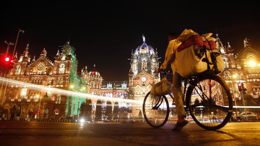 In this Saturday, Dec. 5, 2015 photo, an Indian cyclist waits in front of the landmark Chhatrapati Shivaji train terminus in Mumbai, India. India's financial hub of Mumbai has an annual GDP of about $151 billion, along with some 2.8 million people crammed into low-lying slums that flood regularly. Global losses from flooding in coastal cities are already averaging about $6 billion a year, according to a 2013 study published in the journal Nature. Those losses could rise to $52 billion annually by 2050, it said. (AP Photo/Rajanish Kakade)