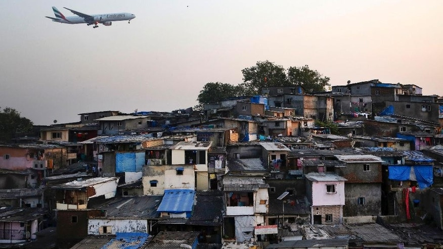 In this Saturday, Dec. 5, 2015 photo, an aircraft flies above the slums near the Chhatrapati Shivaji International Airport in Mumbai, India. India's financial hub of Mumbai has an annual GDP of about $151 billion, along with some 2.8 million people crammed into low-lying slums that flood regularly. Scientists generally agree seas will rise an average of 1 meter (3 feet) this century, though some predict an eventual increase as high as 6 meters on average. (AP Photo/Rajanish Kakade)