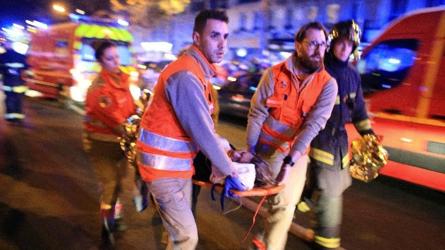 FILE - In this Nov.13, 2015 file photo, a woman is being evacuated from the Bataclan concert hall after a shooting in Paris. All the attackers and accomplices so far identified were raised in Europe, native French speakers with roots in the marginalized immigrant communities of France and Belgium. Minor players, like the man who rented a room to the attacks' mastermind, Abdelhamid Abaaoud, have a degree or two of separation in an underworld of drugs, fraud and theft. (AP Photo/Thibault Camus, File)