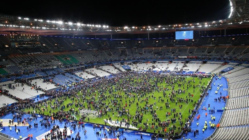 FILE - In this Nov.13, 2015 file photo, spectators invade the pitch of the Stade de France stadium after the international friendly soccer France against Germany, in Saint Denis, outside Paris. All the attackers and accomplices so far identified were raised in Europe, native French speakers with roots in the marginalized immigrant communities of France and Belgium. Minor players _ like the man who rented a room to the attacks' mastermind, Abdelhamid Abaaoud _ have a degree or two of separation in an underworld of drugs, fraud and theft. (AP Photo/Michel Euler, File)